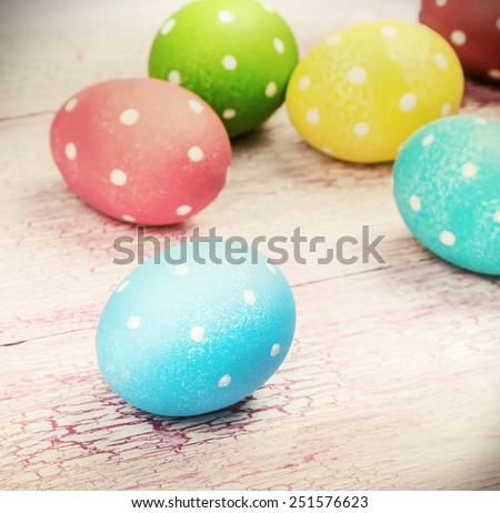 colored Easter eggs on wooden background. Focus on a blue egg. toned photo - stock photo