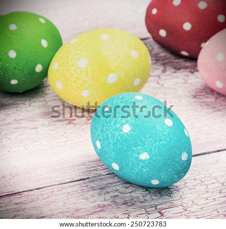 colored Easter eggs on wooden background. Focus on a green egg.toning - stock photo
