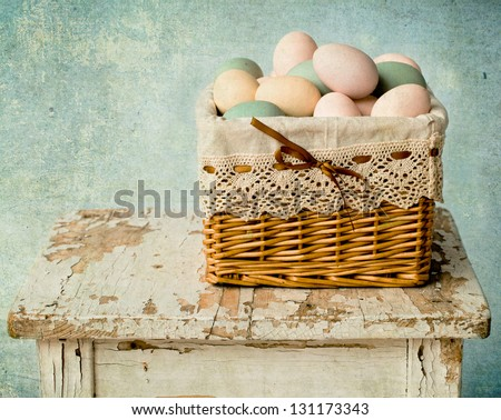 Colored eggs in a basket on the old stool - stock photo