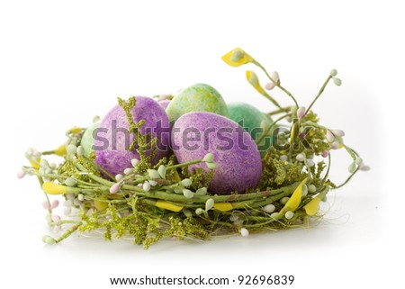 Colored eggs in a easter basket isoliert on white background - stock photo