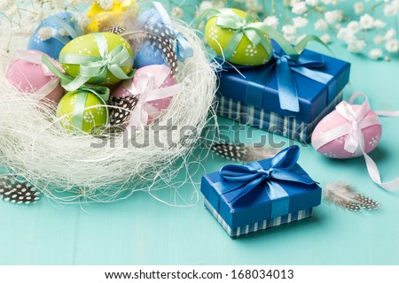 Colored eggs in the nest and presents in blue boxes (horizontal shot) - stock photo
