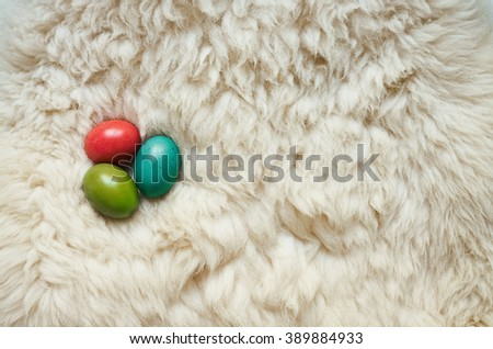 Colored eggs on natural fluffy sheep skin background. Easter postcard template. Space for text, copy, lettering. - stock photo