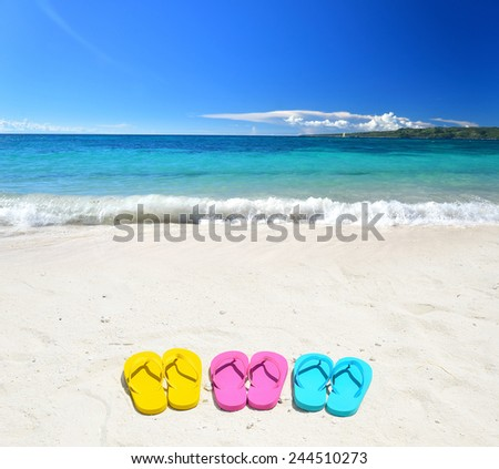Colored flip-flops on the sunny beach -- Concept of tropical holidays - stock photo
