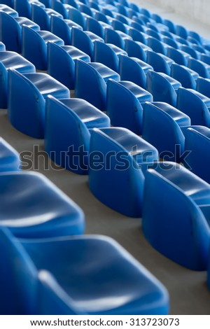 Colored football stadium empty tribune for spectator with a pattern of blue plastic seats - stock photo