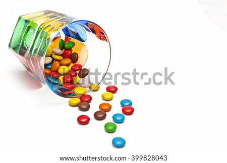Colored glass cup with multicolored candies spilled out isolated on white background with place for your text - stock photo