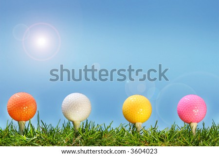 Colored golf balls in the grass - stock photo
