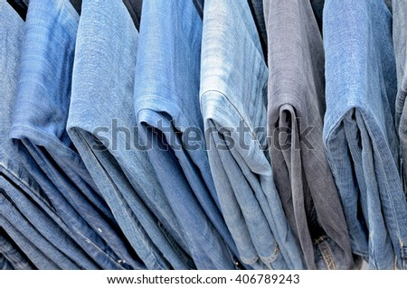 Colored jeans hanging on hangers. Top view. - stock photo