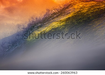 Colored Ocean Wave Falling Down at Sunset Time. - stock photo