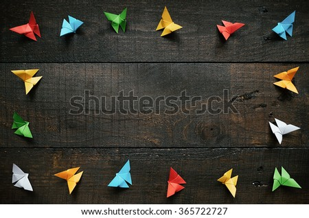 Colored origami paper butterflies frame on dark brown aged wood background. Valentines day horizontal postcard template. Space for copy, text, lettering. - stock photo