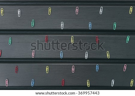 Colored paper clips lie evenly on the table - stock photo