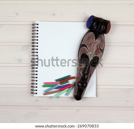 Colored pencils and a mask on a wooden texture - stock photo