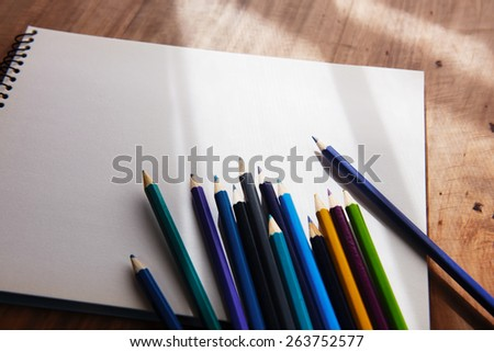 Colored pencils and blank sketch book in by-the-window like light and shadow. Shallow depth of field. - stock photo