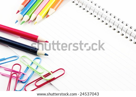 Colored pencils and paperclips on horizontal blank lined index cards with copy space - stock photo