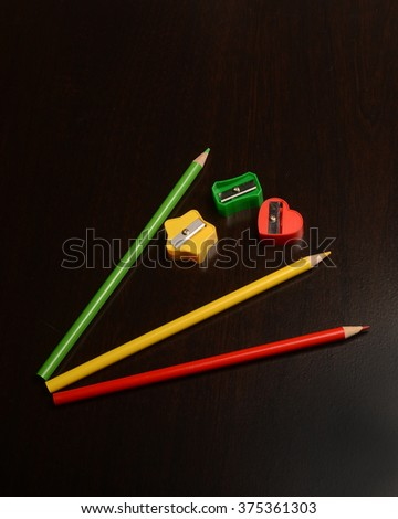 Colored pencils and sharpeners/Pencils and Sharpeners/Pencils and sharpeners on a dark surface - stock photo