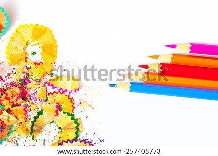 colored pencils and shavings on white background with copy space - stock photo