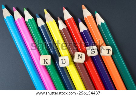 Colored pencils and wood dice with the german word art / Art - stock photo