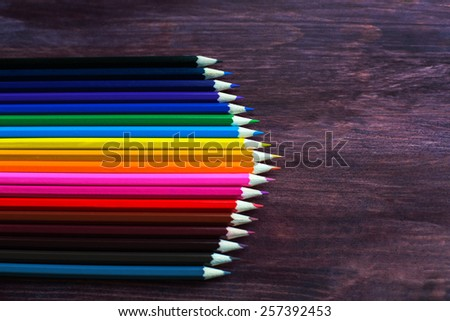 colored pencils in a row on dark background - stock photo