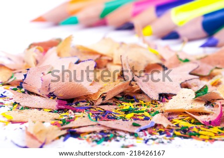 Colored pencils of different colors with a lot of color shavings. Closeup with shallow DOF. Isolated on white background. - stock photo