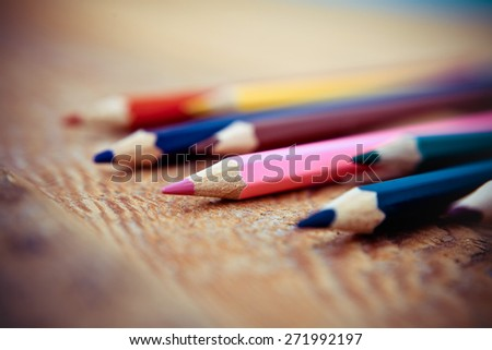 Colored pencils on a wooden background. Vintage - stock photo