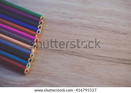 colored pencils on the wooden table edit for vintage tone - stock photo