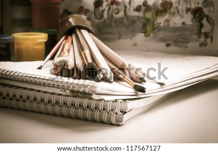 Colored pencils, paint, sketch pad, drawing, brush - stock photo