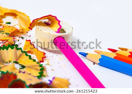 colored pencils, sharpener and shavings on white background with copy space. - stock photo