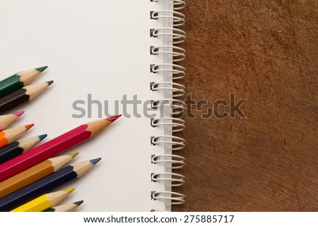 Colored Pencils with notebook, isolated on wood background, may use as banner or slide - stock photo