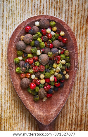 Colored peppers mix on wooden spoon, close up - stock photo