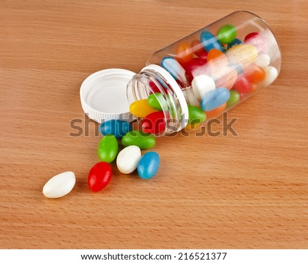 Colored Pills pouring out of the plastic bottle on surface wooden table - stock photo
