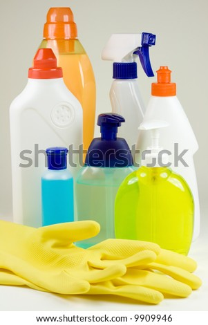 Colored plastic detergent bottles and yellow rubber gloves - stock photo