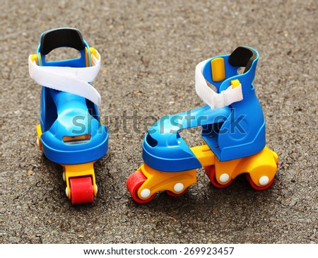 Colored plastic roller skates left in the street       - stock photo