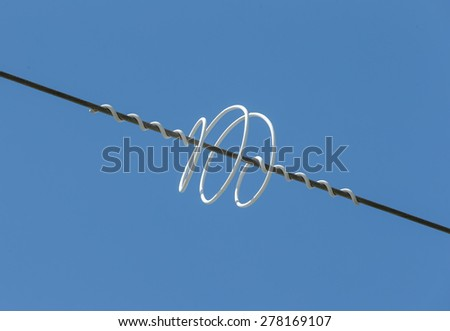 Colored protective spiral mounted on the cable high voltage power lines - stock photo
