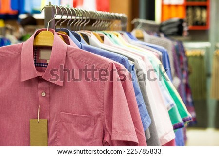 Colored shirts on hangers in a shop - stock photo