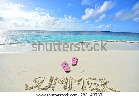 Colored slippers and summer word at the beach -- Tropical beach vacation and travel concept 