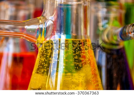 Colored solutions with bubbles in glassware are meaningful for science, chemistry and environment or chemical industry ! - stock photo