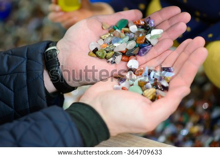 Colored stones in his hands. Round precious and semi-precious minerals.Polished minerals. Beautiful natural stones. People with hand sorted stones. Geology and geography.  A scattering of stones. - stock photo