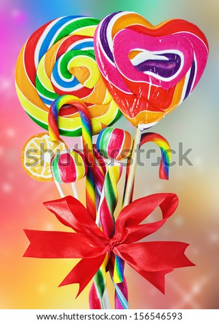 colored sweets with red ribbon bow on a colored background - stock photo
