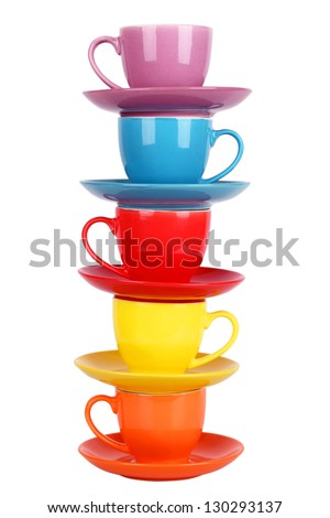 Colored tea cups and saucers, isolated on white - stock photo