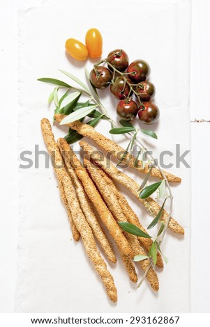colored tomatoes, bread sticks with sesame seeds, olive oil and olive leaf. - stock photo