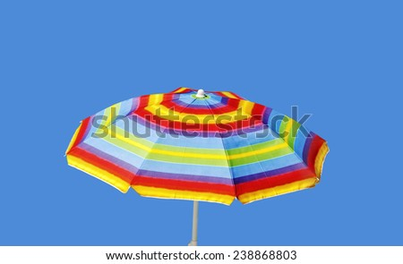 Colored umbrella isolated on blue surface. - stock photo