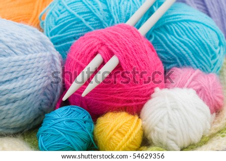 colored wool clews with needles as background - stock photo