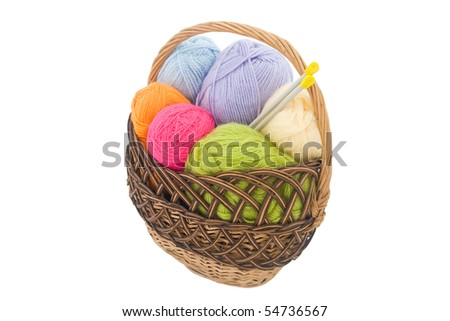 colored wool clews with needles in wicker basket - stock photo