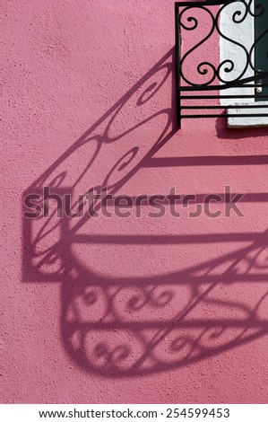 colored wrought iron balcony shadow - stock photo