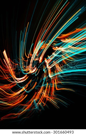 Colorful abstract glowing twirl lines at night - stock photo