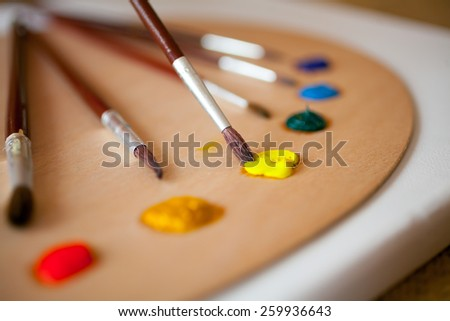 Colorful acrylic paints on wooden pallet. Focus on paintbrush dipped in yellow paint - stock photo