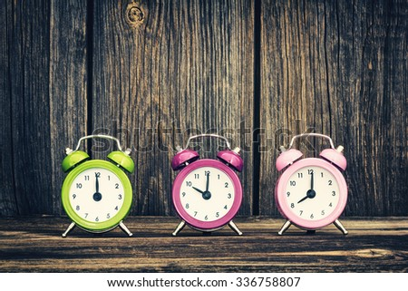 Colorful  alarm clocks showing different time - stock photo