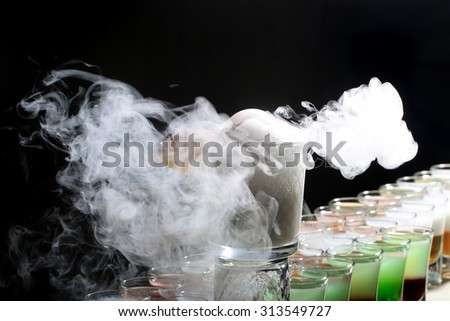 Colorful alcoholic shot cocktails in glasses and one long beverage making reaction of white smoke standing in row on black studio background, horizontal picture - stock photo