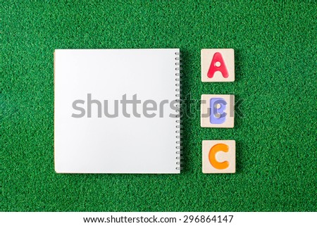 "Colorful alphabet letters ""abc"" ,and the note book on grass background - stock photo"