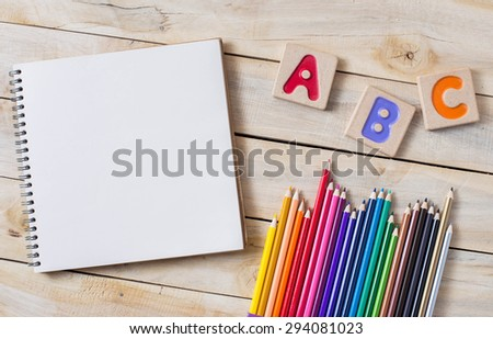 "Colorful alphabet letters ""abc"" ,crayons and the note book on wooden background - stock photo"