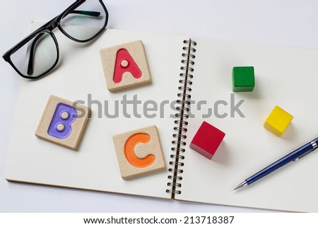 """Colorful alphabet letters ,""""abc"""" ,glasses and a pencil on the book - stock photo"""